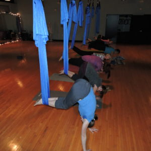 Student in plank and plank roll ups building strength through aerial yoga.